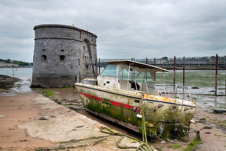 eyesore: An old Martello Tower and a washed up boat at Pembroke Dock on the Pembrokeshire coast in Wales