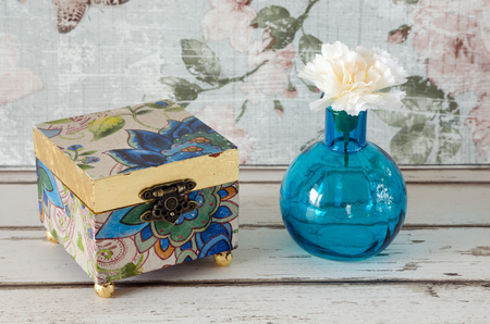 trinket: A handmade gilded trinket box with vase and flower on a shabby chic background