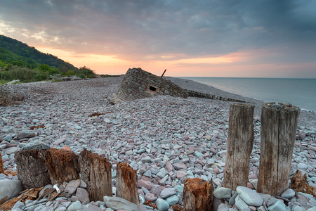 somerset: Stunning sunset over the beach at Porlock Weir in Somerset, with an old WWII bunker in the background Stock Photo