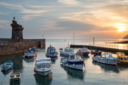 lynton: Stunning sunrise over fishing boats in the harbour at Lymouth on the north coast of Devon