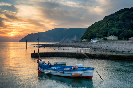 lynmouth: Beautiful sunrise over a boat in the harbour at Lynmouth on the north coast of Devon