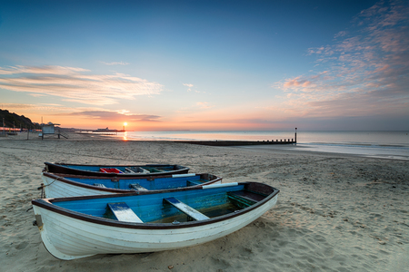 bournemouth: Beautiful sunrise over boats on the beach at Durley Chine in Bournemouth with the pier in the far distance Stock Photo