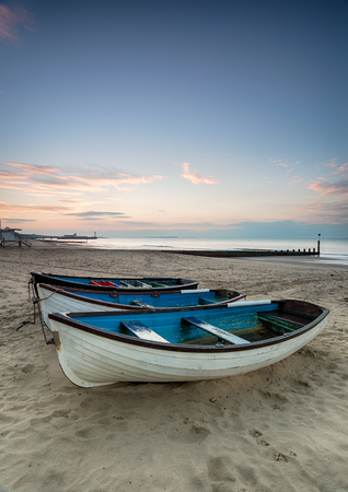 bournemouth: A row of boats at sunrise on Bournemouth beach in Dorset Stock Photo