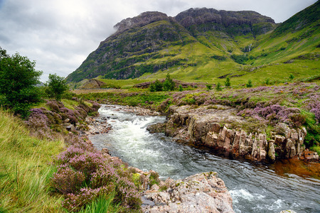 glencoe: The river Coe cascading through the valley below mountains at Glencoe in the Scottish Highlands Stock Photo