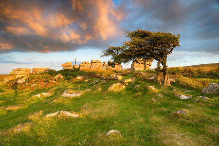 Beautiful evening light and a dramatic sky over Combestone Tor near Hexworthy on Dartmoor National Park in Devon