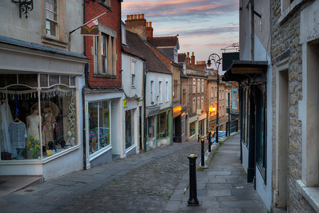 shop window: Dusk on Catherine Hill a cobbled street of historic buildings at Frome in Somerset