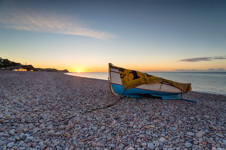 Fishing boat at sunrise on the beach at Budleigh Salterton on the Devon coast