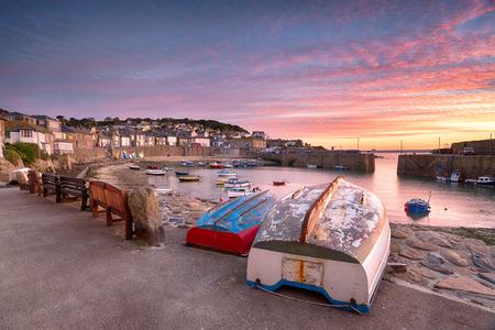 mousehole: Beuatiful sunrise over the harbour at Mousehole near Penzance on the Cornish coast