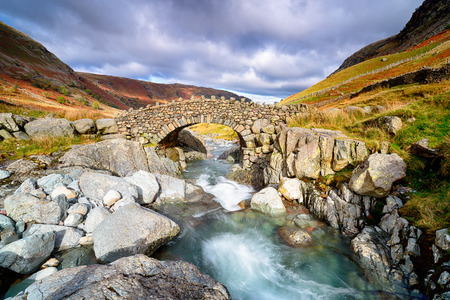 Stocley Bridge crossing the river Derwent near Seathwaite in the Lake District National Park in Cumbria. Stock Photo