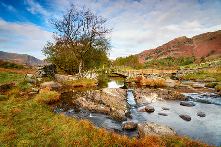 Autumn at Slaters Bridge which spans the river Brathay at Little Langdale in the Lake District in Cumbria