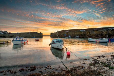 mousehole: Sunrise over fishing boats at Mousehole near Penznance on the Cornwall coast Stock Photo