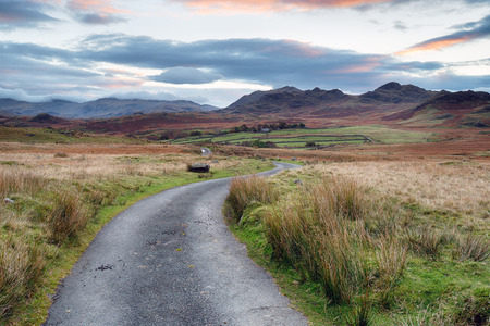 A country road leading to the mountains on Birker Fell and looking towards Scar Crag and Silver How in the Lake District National Park in Cumbria