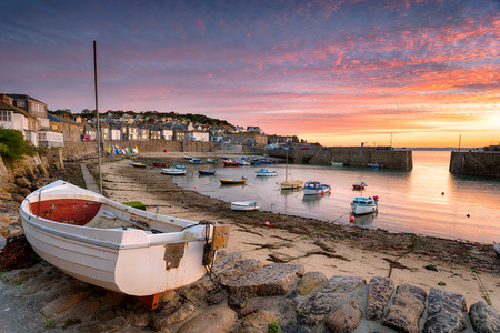 mousehole: Stunning sunrise over fishing boats at Mousehole near Penzance in Cornwall