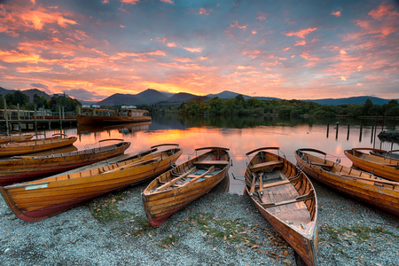 Stunning sunset over wooden rowing boats on Derwentwater at Keswick in the Lake District Nationla Park in Cumbria Stock Photo