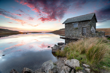 Sunset over an old stone boathouse on the shores of Devoke Water, a remote lake on Birker Fell in the Lake District national park in Cumbria