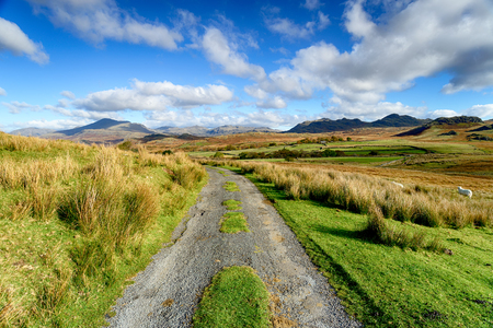 A country lane leading over the moor to mountains at Birker Fell in the Lake District National Park in Cumbria Stock Photo