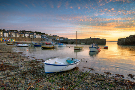 mousehole: Beautiful sunrise over fishing boats in the harbour at Mousehole near Penzance in Cornwall