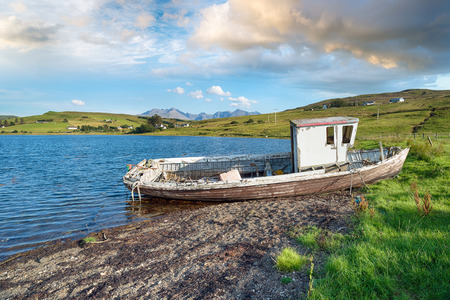 An old fishing boat on the shores of Loch Harport on the Isle of Skye in Scotland Stock Photo