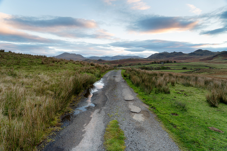cumbria: A lonely country road leading through Birker Fell in the Lake District national park in Cumbria Stock Photo