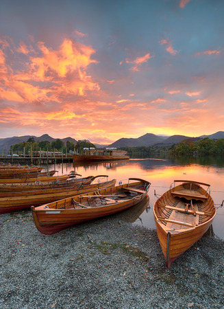 A fiery sunset over boats on the shore of Derwentwater at Keswick in the Lake District Stock Photo