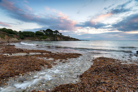 Sunrise at Colona Beach and looking out at Chapel Point, on the South West Coast Path near Portmellon in Cornwall  Stock Photo