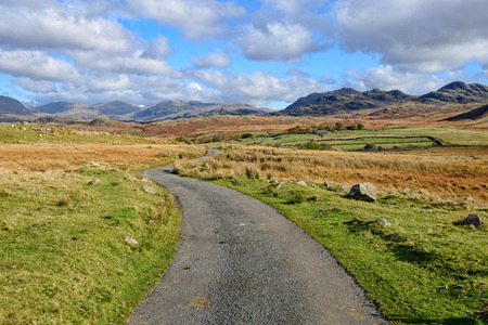 cumbria: A winding country lane leading to mountains on Birker Fell in the Lake District National Park in Cumbria Stock Photo
