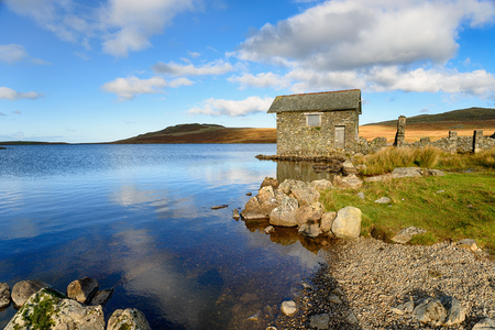 An old stone boat house on the shores of Devoke Water in the Lake Distict in Cumbria