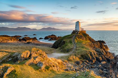 遠くにスノードニア山脈と北ウェールズのアングルシー海岸 Ynys Llanddwyn 島の夕日。