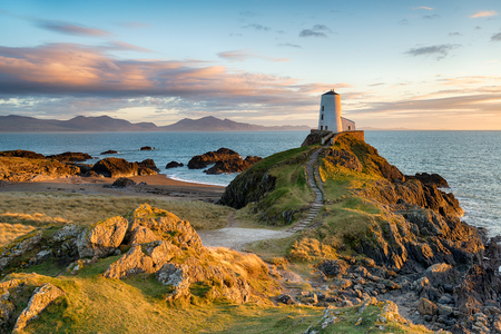 Sunset at Ynys Llanddwyn island on the coast of Anglesey in North Wales with the mountains of Snowdonia in the distance. Banque d'images