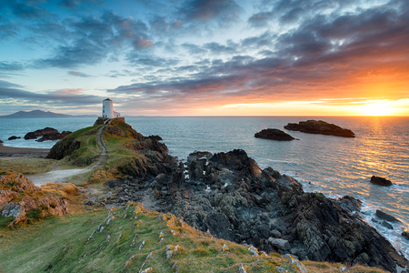 Stunning sunset over the Twr Mawr lighthouse on Ynys Llanddwyn on the Anglesey coast in north Wales Reklamní fotografie