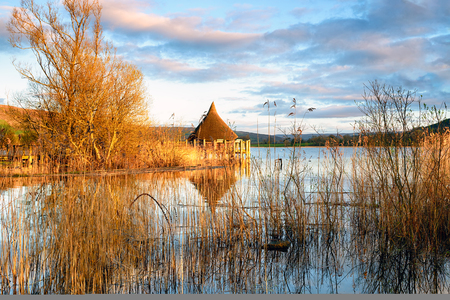 brecon beacons: A thatched hut with a conical roof on stilts called a Crannog at Llangorse Lake in the Brecon Beacons National Park in Wales Stock Photo