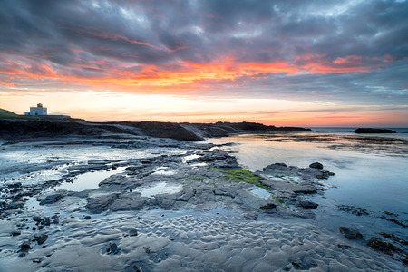 Sunset over the lighthouse and beach at Bamburgh on the Northumberland coast Stock Photo
