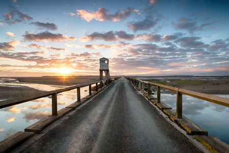 Sunrise over the causeway bridge that links the island of Lindsifarne with the mainland on the Northumbria coast, looking out to the island and the hut used as a refuge for those stranded by the tide.