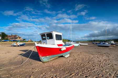 A red fishing boat on the beach at Alnmouth estuary on the Northumberland coast