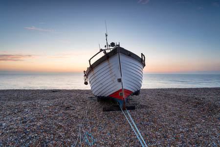 A fishing boat at sunrise on the shores of Dungeness beach on the Kent coast Stock Photo