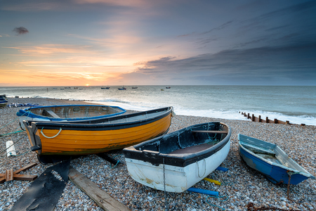 Sunrise over boats on the beach at Selsey in West Sussex