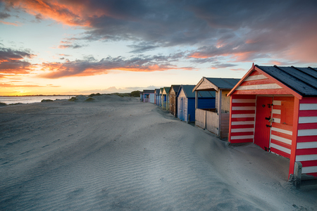 Dramatic sunset over beach huts at West Wittering on the Sussex coastline