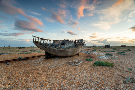An old abandoned fishing boat under a dramatic sky on the beach at Dungeness on the Kent coast