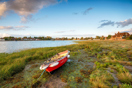 A red boat on the shore at Bosham on the West Sussex coast near Chichester