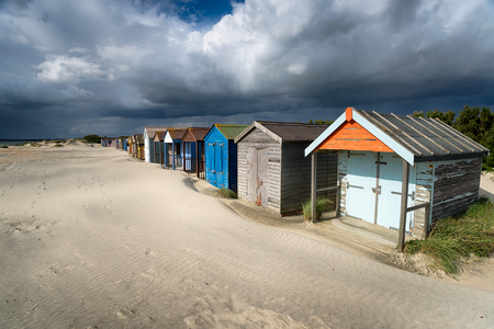 Dramatic sky over beach huts at West Wittering near Chichester on the Sussex coast
