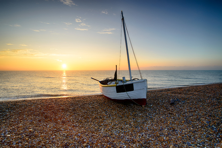 Beautiful sunrise over a fishing boat on the shore at Dungeness beach on the Kent coast
