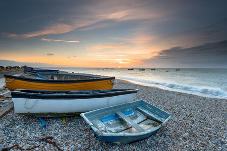 Sunrise over boats on the beach at Selsey on the West Sussex coastline Stock Photo