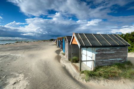 Pretty beach huts under a dramatic sky at West Wittering on the Sussex coast