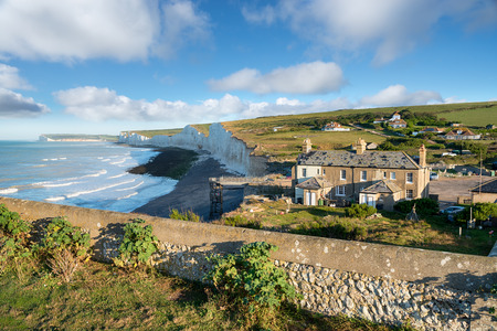 Cottages perilously close to the edge of crumbling cliffs at Birling Gap on the Sussex coast Stock Photo