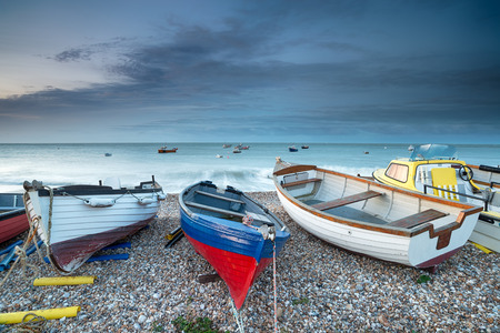 Boats under a stormy sky on the beach at Selsey Bill on the Sussex coast