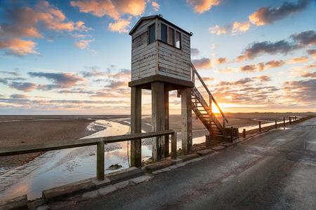 Sunrise over the pilgrim shelter on the Lindifarne causeway on the Northumerland coast