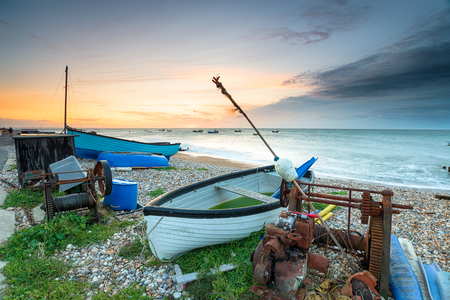 Stormy sunrise over boats on the beach at Selsey Bill on the Sussex coast Archivio Fotografico