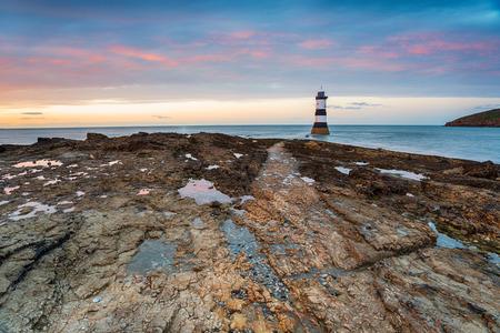Tramonto sul faro di Penmon Point sulla costa di Anglesey Archivio Fotografico
