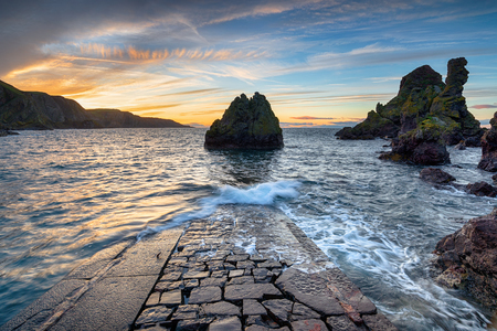 Dramatic sunset over sea stacks and an old stone jetty at Pettico Wick Bay at St Abbs in the Scottish Borders Reklamní fotografie