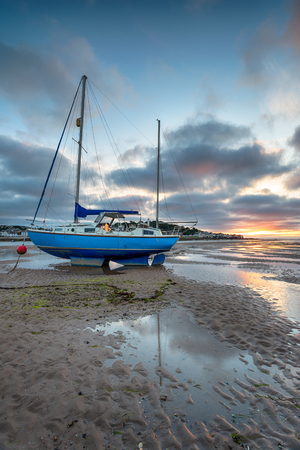 Dramatic sunset sky over a sailing boat at Instow near Bideford on the north coast of Devon Stock Photo